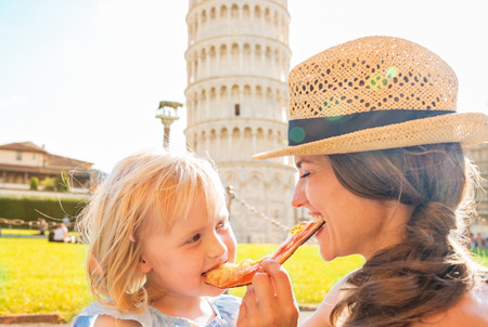 Happy mother and baby girl eating pizza in front of leaning tower of pisa, tuscany, italy Foto de archivo