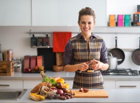 cherokee: Happy young housewife cutting cherokee purple tomato