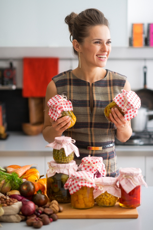 canned peas: Happy young housewife with jars of pickled vegetables