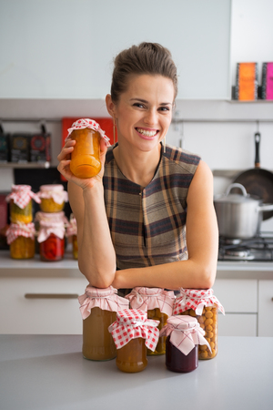 Portrait of happy young housewife among jars with homemade fruits jam and pickled vegetables photo