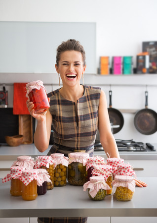 Portrait of happy young housewife among jars with homemade fruits jam and pickled vegetables