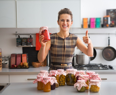 Portrait of happy young housewife among jars with homemade fruits jam and pickled vegetables showing thumbs up Zdjęcie Seryjne