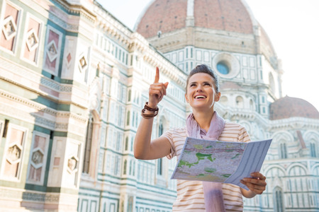 cattedrale: Young woman with map in front of cattedrale di santa maria del fiore in florence, italy pointing
