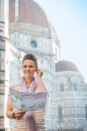 guided: Portrait of happy young woman with map and audio guide in front of cattedrale di santa maria del fiore in florence, italy
