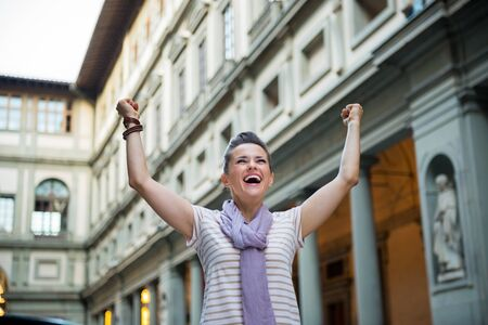 Happy young woman near uffizi gallery rejoicing in florence, italy