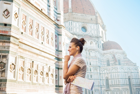 Happy young woman with map and audio guide in front of cattedrale di santa maria del fiore in florence, italy