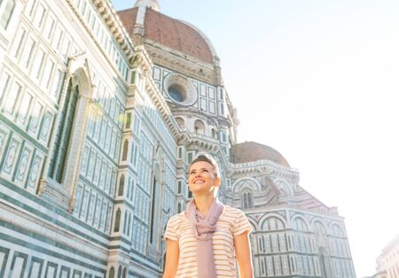 fiore: Happy young woman in front of cattedrale di santa maria del fiore in florence, italy