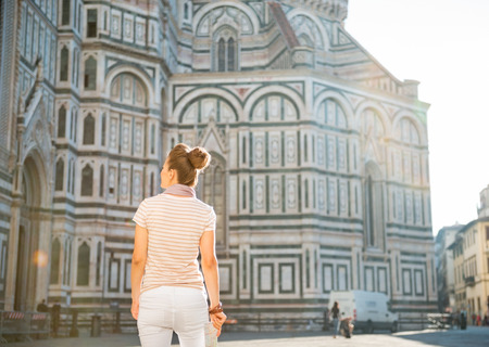 cattedrale: Young woman standing with map in front of cattedrale di santa maria del fiore in florence, italy. rear view