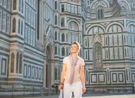 cattedrale: Young woman standing with map in front of cattedrale di santa maria del fiore in florence, italy