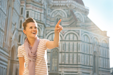 cattedrale: Portrait of happy young woman pointing on copy space in front of cattedrale di santa maria del fiore in florence, italy Stock Photo