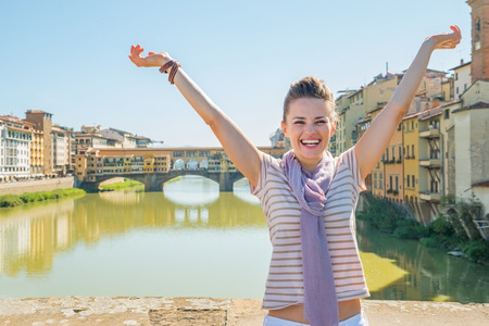 rejoicing: Happy young woman standing on bridge overlooking ponte vecchio in florence, italy and rejoicing