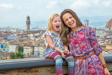 Portrait of smiling mother and baby girl against panoramic view of florence, italy