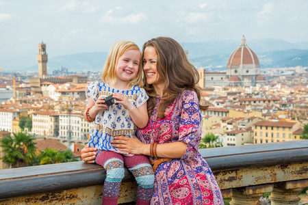 Happy mother and baby girl with photo camera against panoramic view of florence, italy