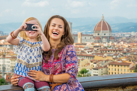 Mother Mary: Happy mother and baby girl taking photo against panoramic view of florence, italy