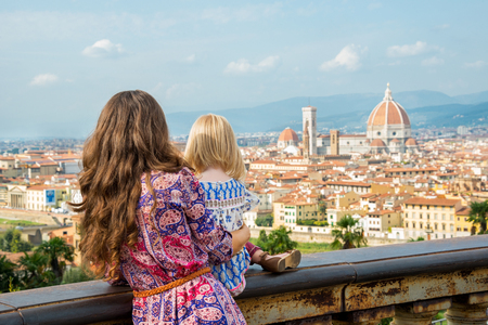 anonym: Mother and baby girl looking on panoramic view of florence, italy. rear view Stock Photo