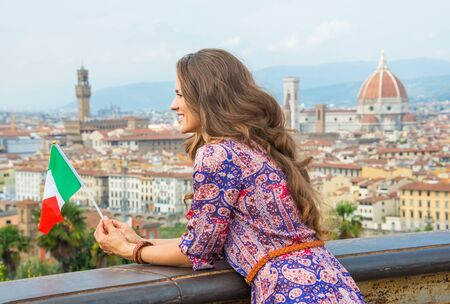 Happy young woman with flag looking into distance against panoramic view of florence, italy photo
