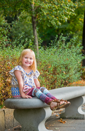 citypark: Portrait of smiling girl sitting on bench in city park