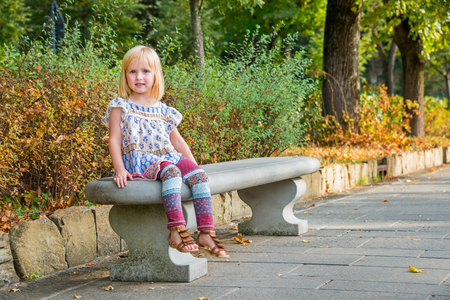 citypark: Portrait of girl sitting on bench in city park Stock Photo