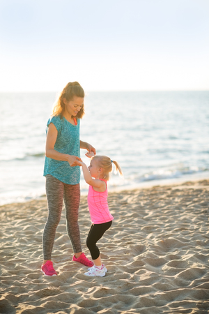mam: Healthy mother and baby girl having fun time on beach in the evening Stock Photo