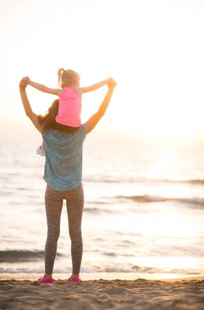 rejoicing: Baby girl sitting on shoulders of mother and rejoicing while on beach in the evening. rear view