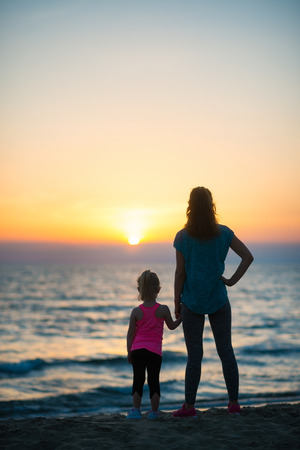 Silhouette of mother and baby girl on beach looking into distance. rear view