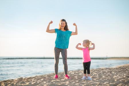 Gesunde Mutter und Baby Mädchen zeigt Bizeps am Strand
