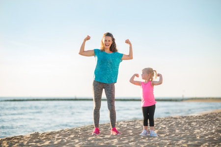 mom and kids: Healthy mother and baby girl showing biceps on beach