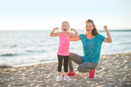 Egészséges anya és a baba lány megmutatja bicepsz a strandon