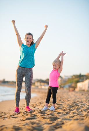 rejoicing: Healthy mother and baby girl rejoicing in the evening on beach Stock Photo