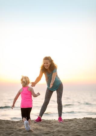 Mother and baby girl having fun time on beach in the evening photo