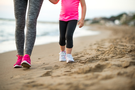 walking baby: Healthy mother and baby girl walking on beach in the evening Stock Photo