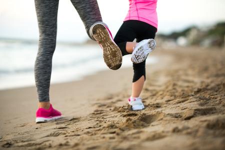 Close-up op een gezonde moeder en baby meisje training op het strand in de avond