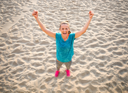 rejoicing: Full length portrait of fitness young woman rejoicing on beach