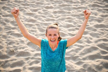rejoicing: Portrait of fitness young woman rejoicing on beach Stock Photo
