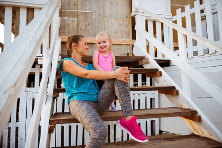 mam: Healthy mother and baby girl sitting on stairs of beach house