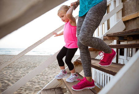 girl in sportswear: Healthy mother and baby girl walking down the stairs Stock Photo
