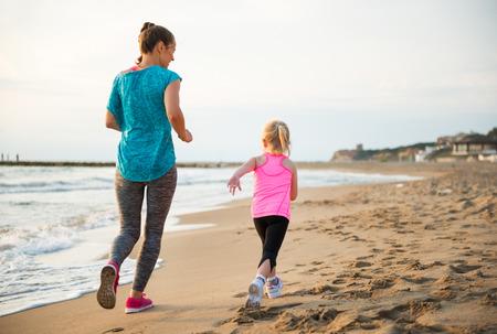 健康な母親とビーチを走る女の子の赤ん坊。リアビュー