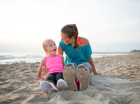 surprised baby: Portrait of fitness mother and surprised baby girl sitting on beach