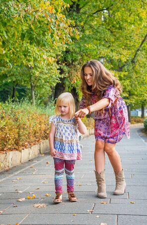 mujeres y niños: La niña y la madre señala en algo mientras se camina en el parque de la ciudad Foto de archivo