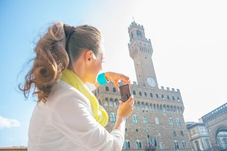anonym: Young woman taking photo of palazzo vecchio in florence, italy. rear view Stock Photo