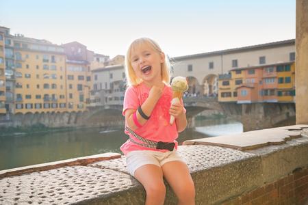 comiendo helado: Bebé feliz que come el helado cerca de Ponte Vecchio en Florencia, Italia Foto de archivo