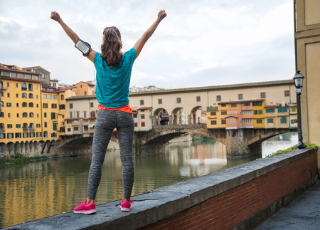 Fitness woman rejoicing in front of ponte vecchio in florence, italy. rear view Stock Photo