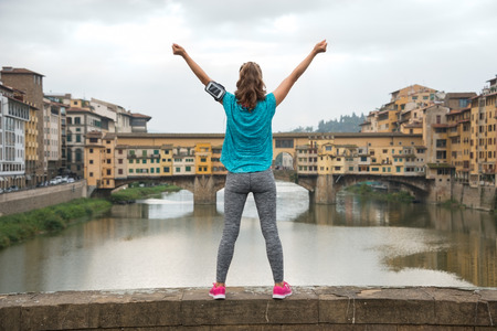 rejoicing: Fitness woman rejoicing in front of ponte vecchio in florence, italy. rear view Stock Photo