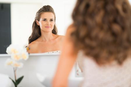 Happy jonge vrouw op zoek in de spiegel in de badkamer Stockfoto