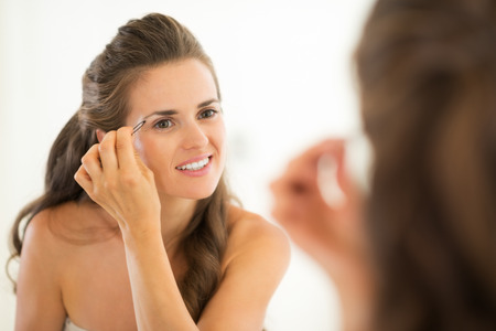 tweezing eyebrow: Happy young woman shaping eyebrows in bathroom