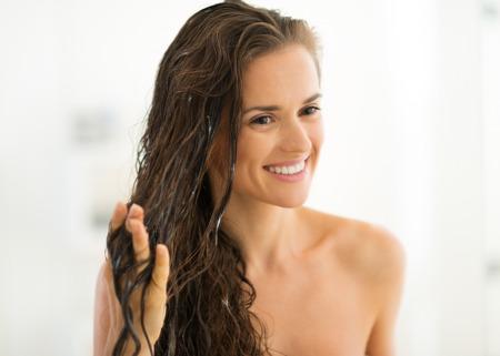 욕실에 헤어 마스크를 적용하는 행복 한 젊은 여자의 초상화