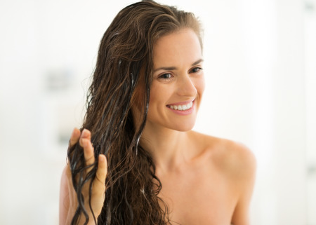 apply: Portrait of happy young woman applying hair mask in bathroom