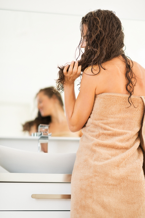 anonym: Young woman with wet hair in bathroom. rear view Stock Photo