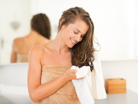 cabello: Mujer joven feliz que limpia el cabello con una toalla en el baño