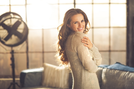 A smiling brunette woman in comfortable clothing is standing in a loft living room, hugging herself while looking over her shoulder. Urban chic loft decoration details.